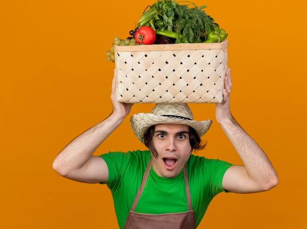 オレンジ色の壁の上に立っている幸せそうな顔で笑顔に見える頭に野菜でいっぱいの木枠を保持しているエプロンと帽子の若い庭師の男
