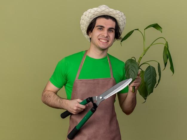 Молодой садовник в фартуке и шляпе держит ножницы для живой изгороди и растение, глядя в камеру с улыбкой на лице, стоя на светлом фоне