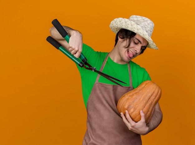 オレンジ色の背景の上に立っている舌を突き出しているヘッジクリッパーでカボチャの切断を保持しているエプロンと帽子の若い庭師の男