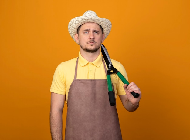 真剣な自信を持って表情で肩にヘッジクリッパーを保持しているジャンプスーツと帽子の若い庭師の男