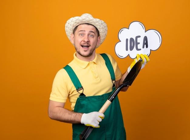 シャベルとスピーチバブルサインを保持しているジャンプスーツと帽子の若い庭師の男は幸せそうな顔で笑顔の単語のアイデア