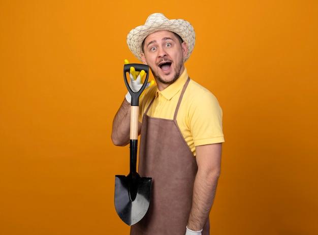 驚いて幸せなシャベルを保持しているジャンプスーツと帽子の若い庭師の男