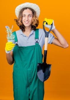 ジャンプスーツとシャベルを保持している帽子を身に着けているゴム手袋の若い庭師の男