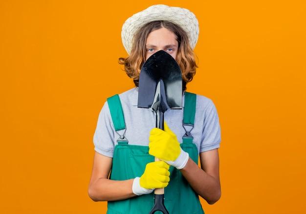 Молодой садовник в резиновых перчатках в комбинезоне и шляпе держит лопату
