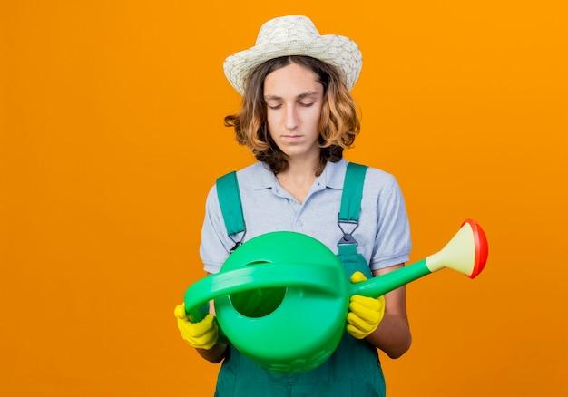 ジャンプスーツと水やりを保持している帽子を身に着けているゴム手袋の若い庭師の男は、オレンジ色の背景の上に立っている深刻な顔でそれを見ることができます