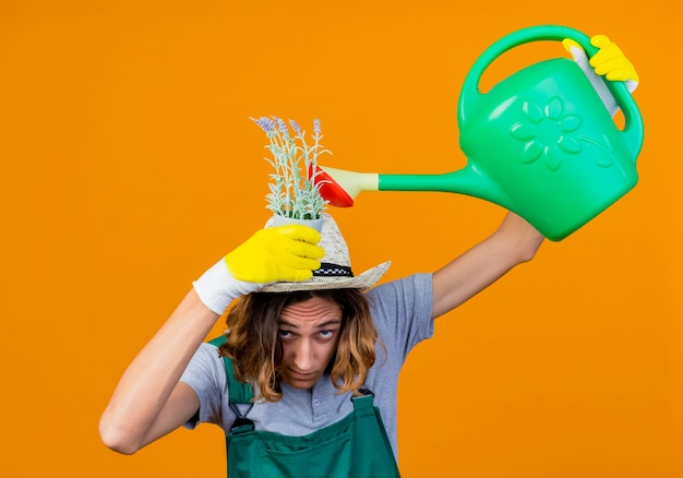オレンジ色の背景の上に立っている彼の頭の上にじょうろ水まき植物を保持しているジャンプスーツと帽子を身に着けているゴム手袋の若い庭師の男