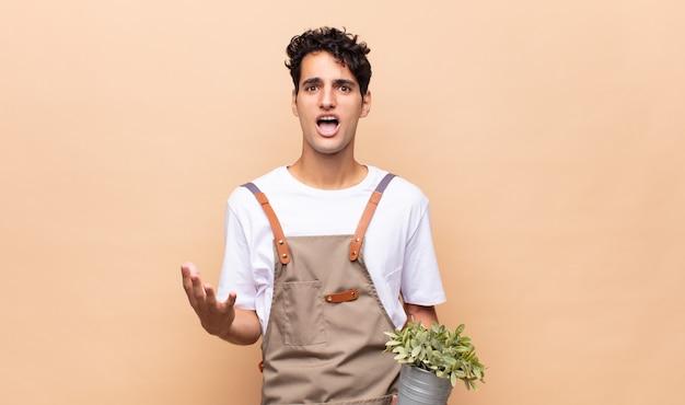 絶望的で欲求不満、ストレス、不幸、イライラ、叫び、叫んでいる若い庭師の男