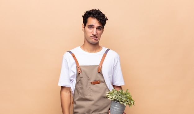 Молодой садовник выглядит озадаченным и сбитым с толку, нервно прикусывает губу, не зная ответа на вопрос