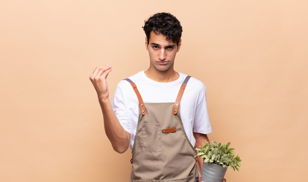 젊은 정원사 남자 capice 또는 돈 제스처를 만들고, 빚을 갚으라고!