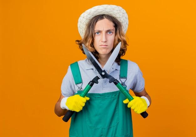 Giovane giardiniere uomo in guanti di gomma che indossa tuta e cappello che tiene tagliasiepi