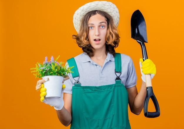 Giovane giardiniere uomo in guanti di gomma che indossa tuta e cappello tenendo la pala