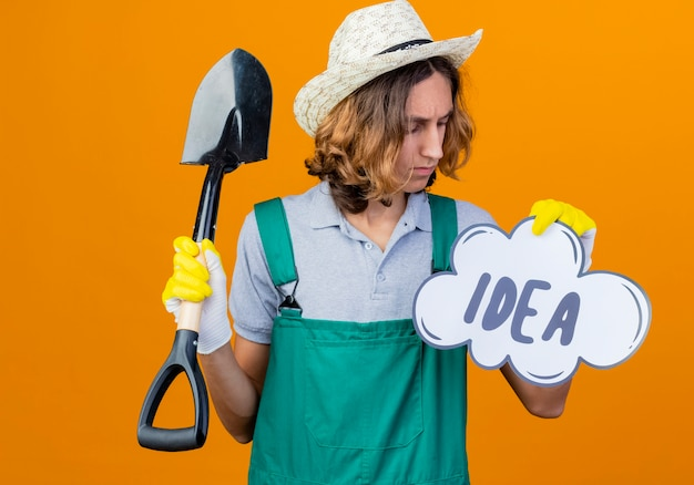 Young gardener man in rubber gloves wearing jumpsuit holding shovel and speech bubble