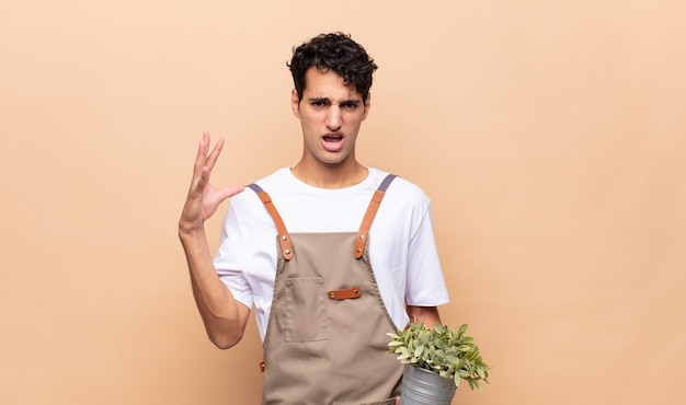 Young gardener man screaming with hands up in the air, feeling furious, frustrated, stressed and upset