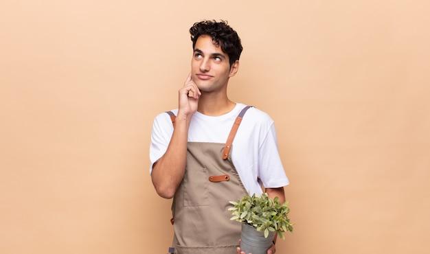 幸せに笑って、空想または疑って、側を見て若い庭師の男