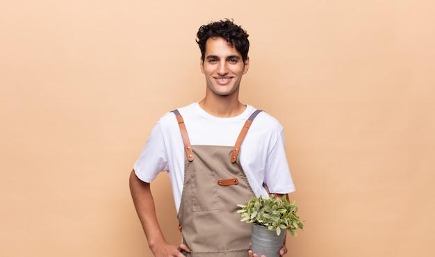 엉덩이와 자신감, 긍정적이고 자랑스럽고 친절한 태도에 손으로 행복하게 웃고있는 젊은 정원사 남자