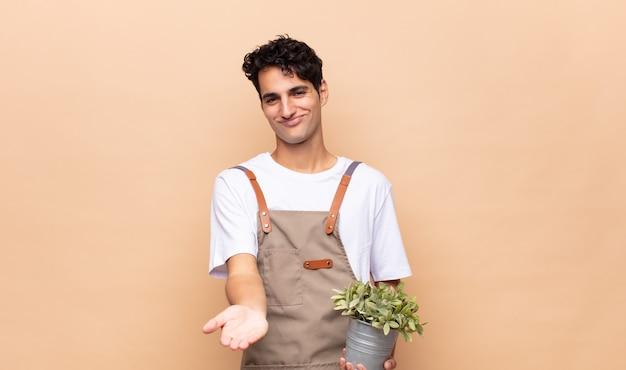 フレンドリーで自信に満ちた、前向きな表情で幸せそうに笑って、オブジェクトやコンセプトを提供し、示す若い庭師の男