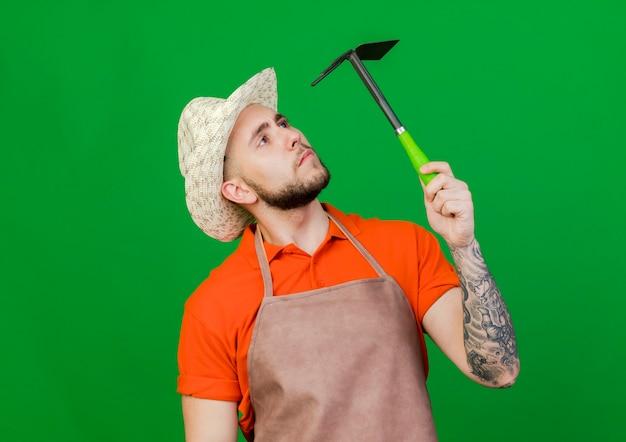 Il giovane giardiniere uomo che indossa il cappello da giardinaggio tiene e guarda il rastrello zappa