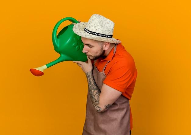 Giovane giardiniere uomo che indossa il cappello da giardinaggio si leva in piedi lateralmente tenendo annaffiatoio guardando verso il basso