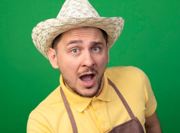 驚いたジャンプスーツと帽子をかぶった若い庭師の男