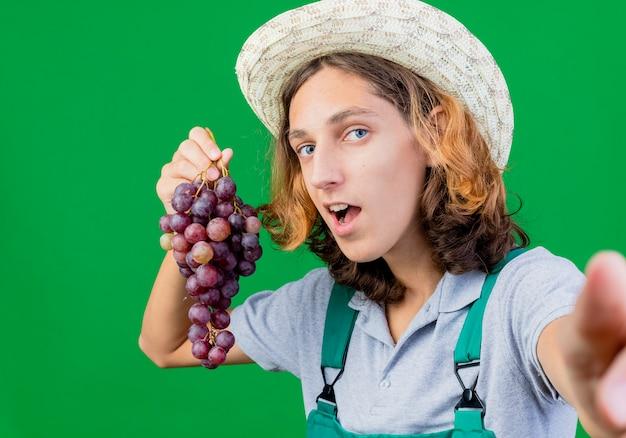 ブドウの笑顔の束を保持しているジャンプスーツと帽子を身に着けている若い庭師の男
