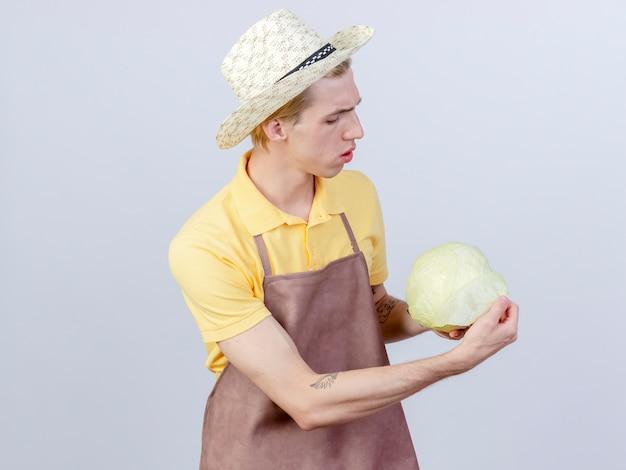 Молодой садовник в комбинезоне и шляпе с капустой смотрит на него с удивлением