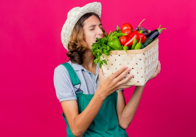 점프 슈트와 신선한 야채로 가득 찬 상자를 들고 모자를 쓰고 젊은 정원사 남자