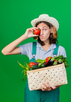 Молодой садовник в комбинезоне и шляпе держит ящик, полный свежих овощей
