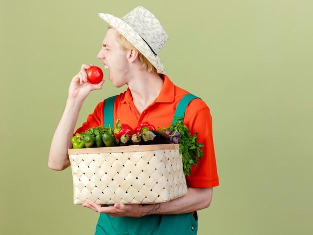 明るい背景の上に立っている新鮮なトマトを噛む野菜でいっぱいの木枠を保持しているジャンプスーツと帽子を身に着けている若い庭師の男
