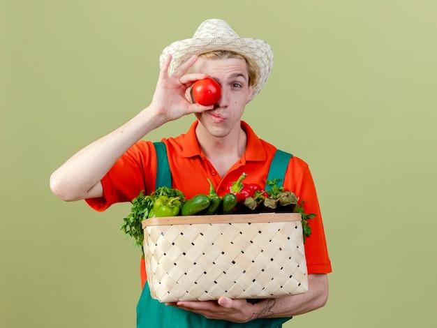 明るい背景の上に立って笑顔のトマトで目を覆う野菜でいっぱいの木枠を保持しているジャンプスーツと帽子を身に着けている若い庭師