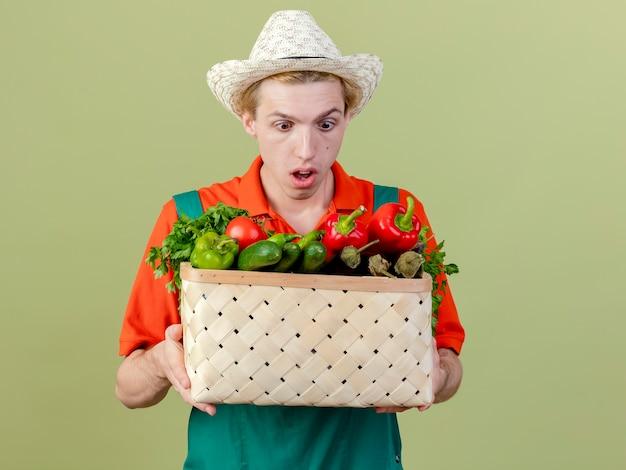 明るい背景の上に立って驚いて驚いたように見える野菜でいっぱいの木枠を保持しているジャンプスーツと帽子を身に着けている若い庭師の男