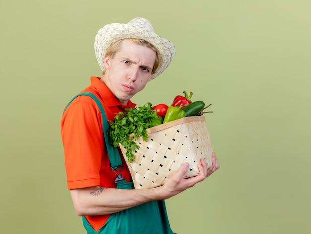 明るい背景の上に立って真面目な顔をしかめているカメラを見て野菜でいっぱいの木枠を保持しているジャンプスーツと帽子を身に着けている若い庭師の男