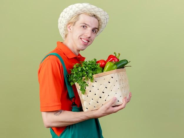 明るい背景の上に立っている顔に笑顔でカメラを見て野菜でいっぱいの木枠を保持しているジャンプスーツと帽子を身に着けている若い庭師の男