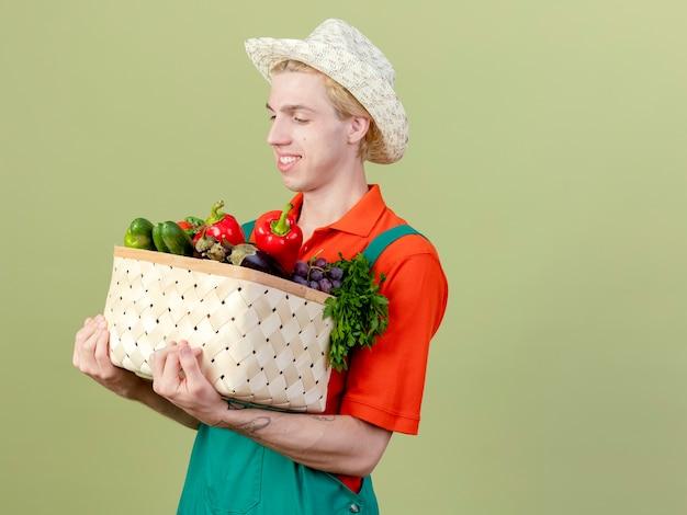 明るい背景の上に立っている顔に笑顔で野菜を見て野菜でいっぱいの木枠を保持しているジャンプスーツと帽子を身に着けている若い庭師の男