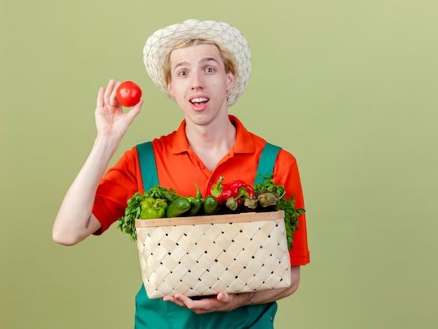 明るい背景の上に立って幸せそうな顔でトマトの笑顔を示す野菜でいっぱいの木枠を保持しているジャンプスーツと帽子を身に着けている若い庭師の男