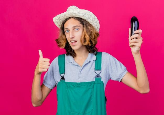 Молодой садовник в комбинезоне и шляпе держит свежие баклажаны