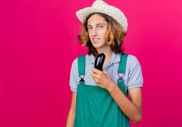 新鮮なナスを保持しているジャンプスーツと帽子を身に着けている若い庭師の男