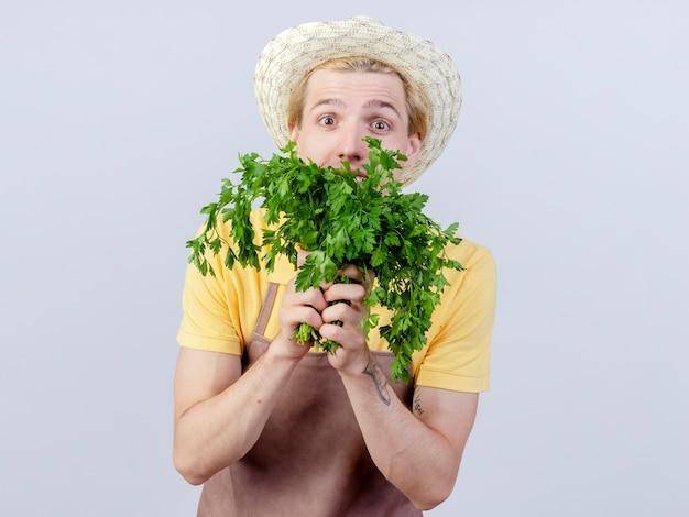 驚いている新鮮なハーブを保持しているジャンプ スーツと帽子を着た若い庭師の男
