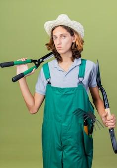 Молодой садовник в комбинезоне и шляпе с садовым инвентарем