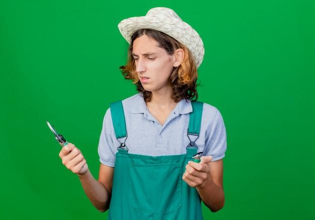 ガーデニング機器を保持しているジャンプスーツと帽子を身に着けている若い庭師の男