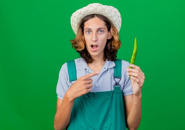 緑の唐辛子を指しているジャンプスーツと帽子をかぶっている若い庭師の男