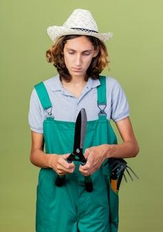ヘッジクリッパーを保持しているジャンプスーツと帽子を身に着けている若い庭師の男