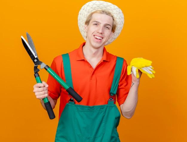 Молодой садовник в комбинезоне и шляпе держит ножницы для живой изгороди и резиновые перчатки, глядя в камеру, весело улыбаясь, со счастливым лицом, стоящим на оранжевом фоне