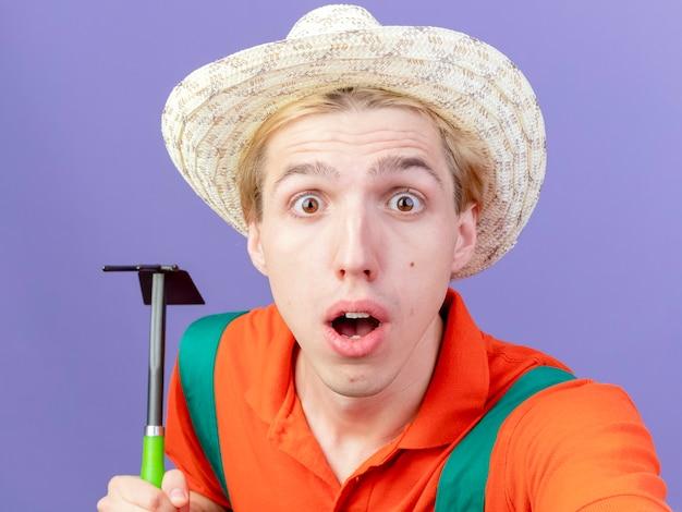 Молодой садовник в комбинезоне и шляпе, держащий мотыгу, глядя в камеру, удивлен и удивлен, стоя на фиолетовом фоне