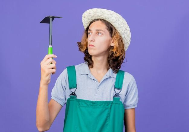 Молодой садовник в комбинезоне и шляпе, держащий мотыгу, смотрит на него серьезно