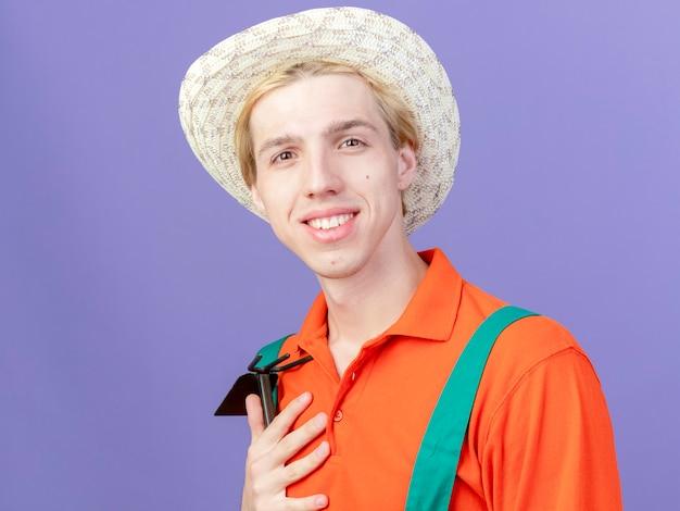 ジャンプスーツと帽子をかぶったマットックを身に着けている若い庭師の男