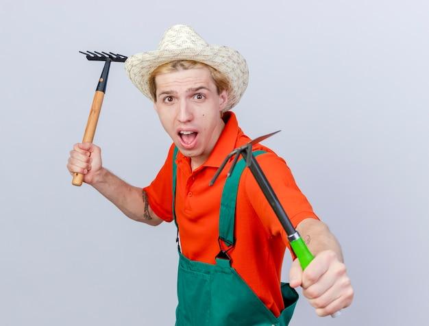 白い背景の上に立っている恐怖の表情で叫んでいるカメラを見てミニ熊手とマトックを保持しているジャンプスーツと帽子を身に着けている若い庭師の男