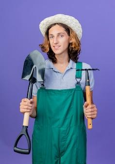 ミニ熊手とシャベルを保持しているジャンプスーツと帽子を身に着けている若い庭師の男