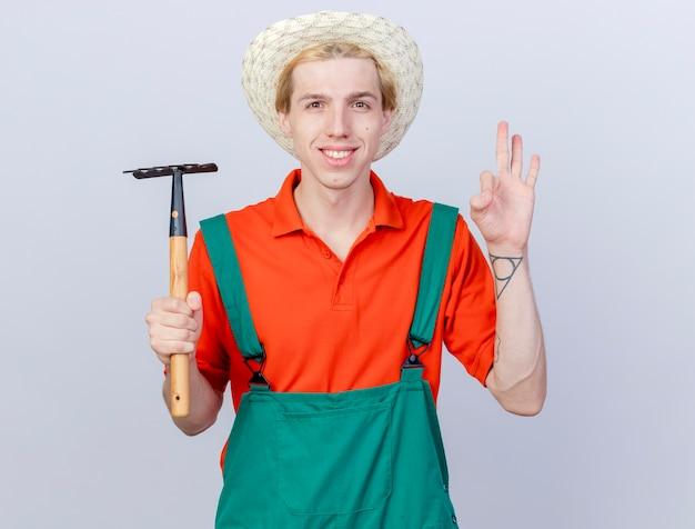Молодой садовник в комбинезоне и шляпе, держащий мини-грабли, смотрит в камеру, весело улыбаясь и позитивно показывая знак ок, стоящий на белом фоне