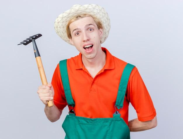 Молодой садовник в комбинезоне и шляпе держит мини-грабли, глядя в камеру, улыбаясь со счастливым лицом, стоящим на белом фоне