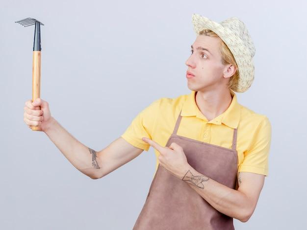 Молодой садовник в комбинезоне и шляпе, держащий мини-грабли, смотрит на него с серьезным лицом, указывая указательным пальцем